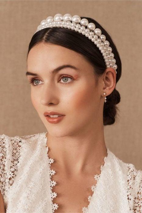 Chica con recogido bajo pulido con diadema de perlas