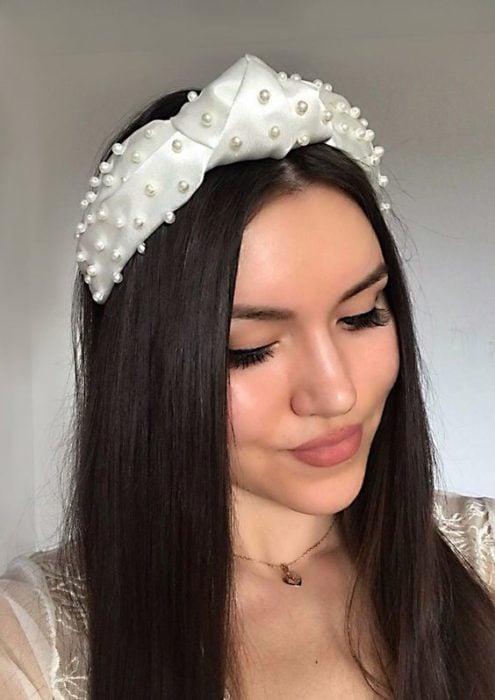 Chica morena con cabello negro suelto y diadema blanca con perlas