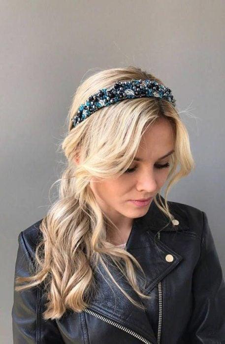 Chica rubia con coleta baja despeinada y diadema azul con piedras