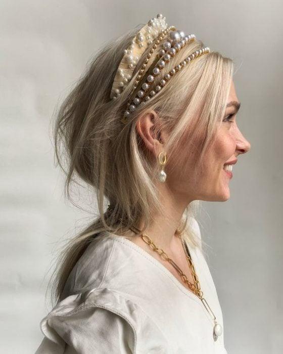 Chica rubia con melena corta usando tres diademas de perlas
