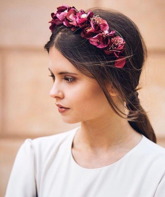 Chica con melena larga y castaña con diadema roja con flores