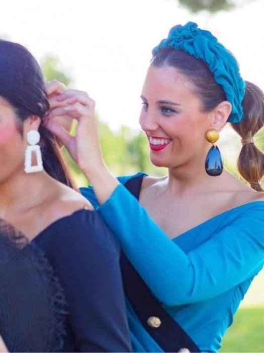 Chica usa vestido, aretes y diadema color azules con cola de peinado