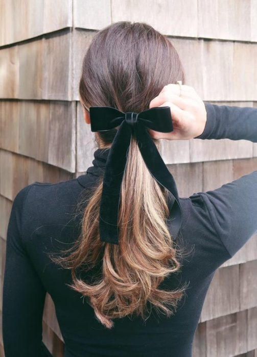 Girl with low ponytail fastened with a navy blue bow
