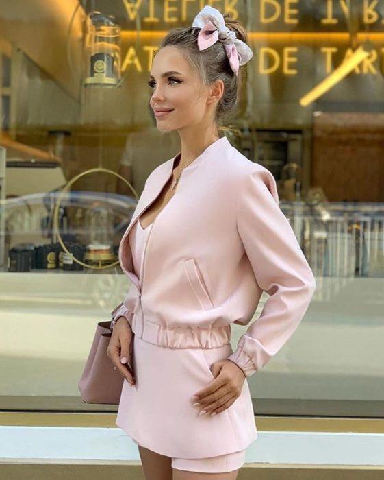 Chica rubia delgada con atuendo rosa y chongo alto con un moño rosa