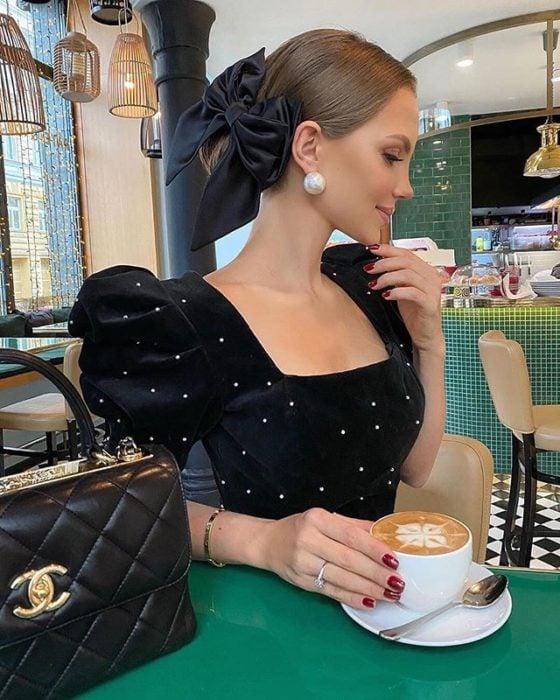 Chica rubia con blusa negra de brillos con chongo y moño negro