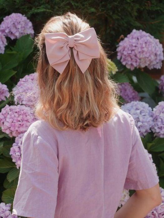 Chica rubia de espladas con cabello en media cola con moño rosa
