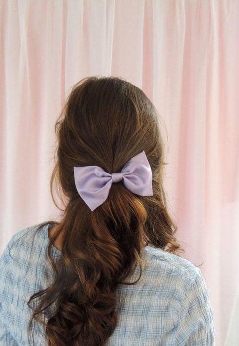 Chica de melena castaña con moño lila