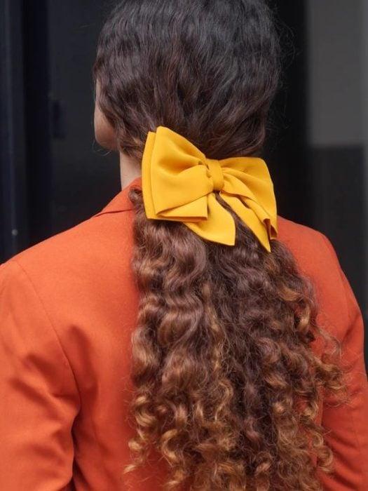 Chca rizada de cabello largo con moño amarillo en una coleta