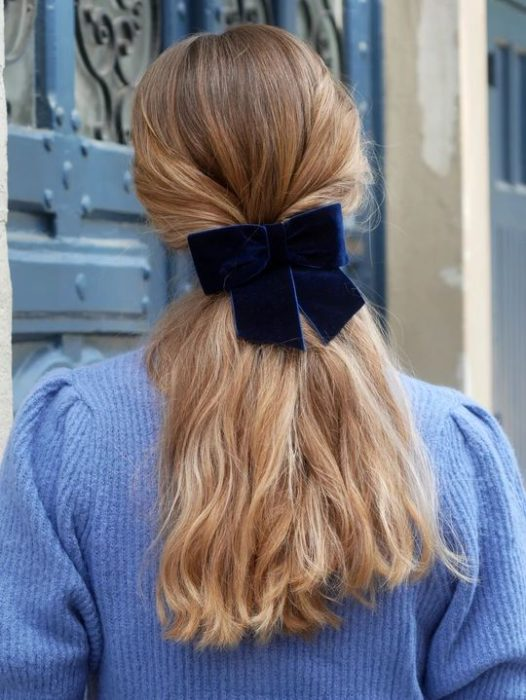 Chica rubia de cabello largo con coleta baja con moño negro