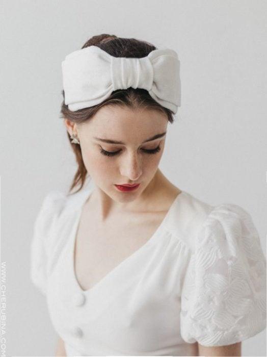 Chica de piel clara con blusa blanca y diadema blanca de moño