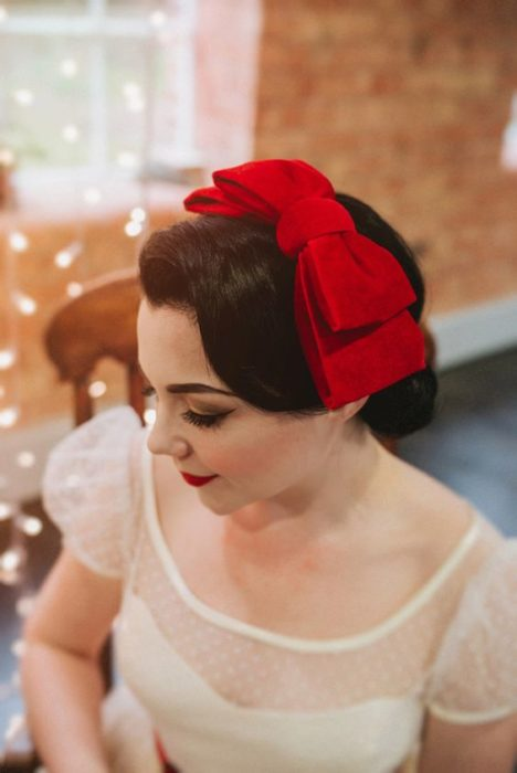 Dark haired girl with pin up hairstyle with big red bow