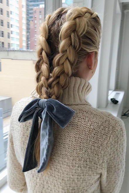 Chica rubia con trenzas alemanas amarradas con moño azul de terciopelo