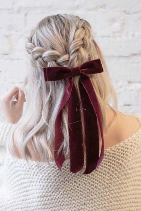 Chica rubia con media coleta de trenzas agarradas en un moño guinda