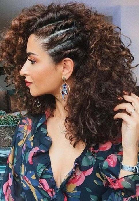 Mujer de cabello rizado con torciditos pegados en un lateral