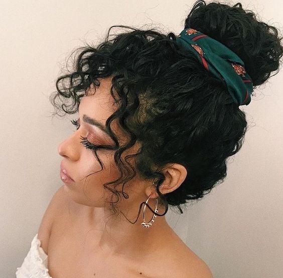 Chica morena de cabello rizado con recogido alto decorado con un pañuelo