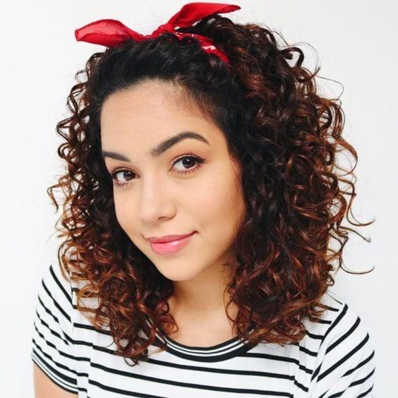Chica de cabello rizado con blusa de rayas blanca con negro y una banda rosa en la cabeza