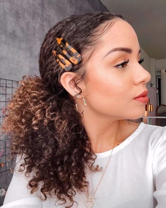 Chica morena de cabello rizado con coleta sujetada con dos borches cafés laterales