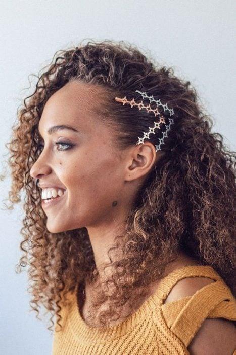 Chica morena de cabello rizado con broches laterales sujetando su cabello