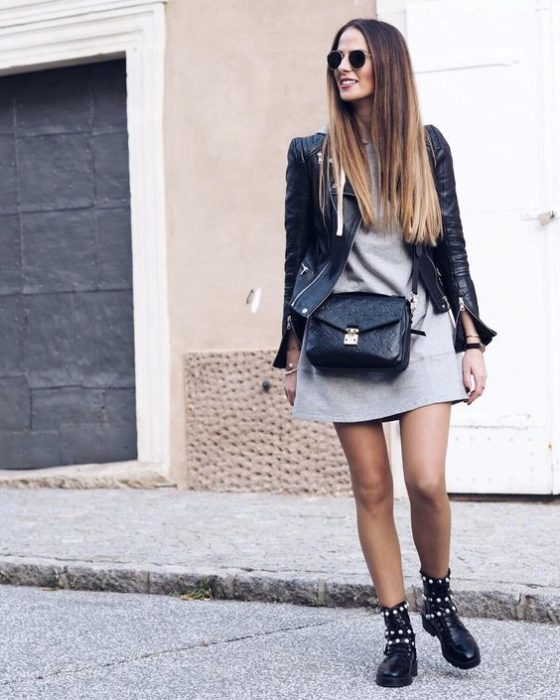 Girl in gray dress, black leather jacket and ankle boots with studs