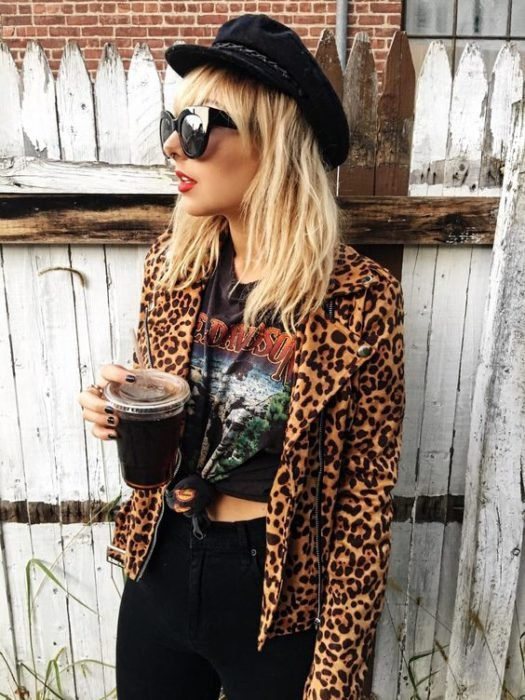 Blonde girl with blonde in black beanie, animal print jacket and black blouse