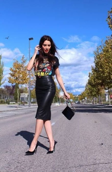 Tall slim woman wears black blouse and leather pencil skirt