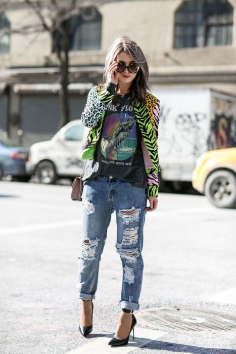 Girl with ripped jeans, black blouse and green animal print jacket