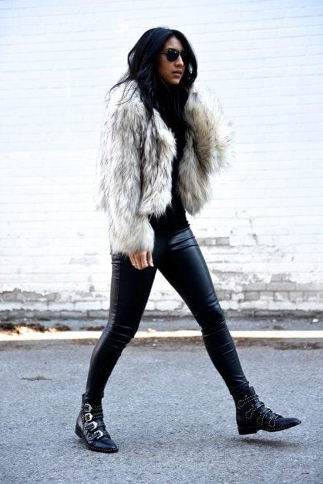 Chica caminando con pantalón de cuero negro y saco de piel blanco