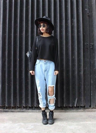 Girl in ripped pants, black sweater and black hat