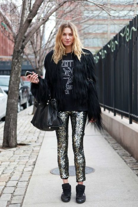 Blonde girl in black blouse, black furry coat and shiny pants