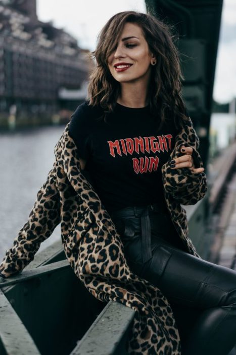 Chica con outfit negro y abrigo de leopardo sentada
