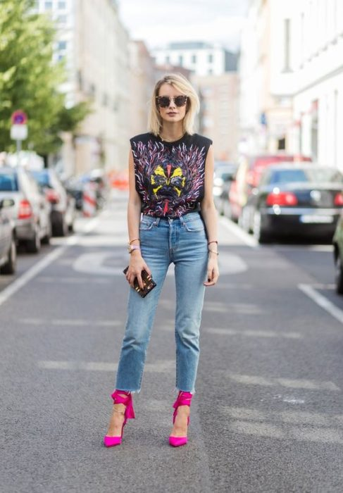 Blonde short hair girl in jean and black sleeveless top with rock band print
