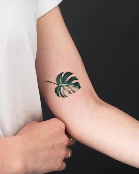 Tatuaje de flores en el brazo de la hoja de una planta