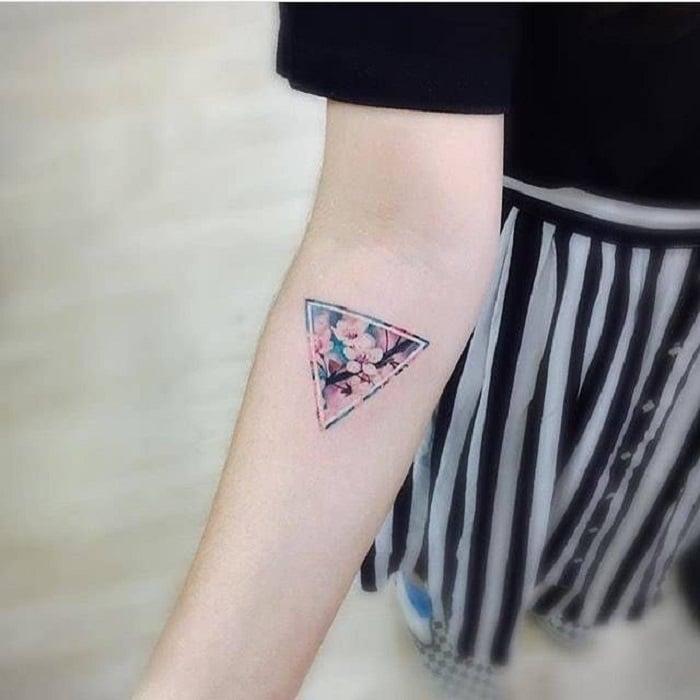 Tatuaje de flores en el antebrazo en forma de un triángulo con margaritas