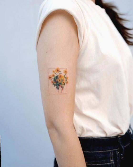 Tatuaje de flores en el que es un ramo de girasoles rodeado de un sutil rectángulo sobre el brazo