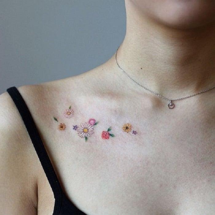 Tatuaje de flores enel que son flores sueltas de diferentes tipos, sobre las clavículas