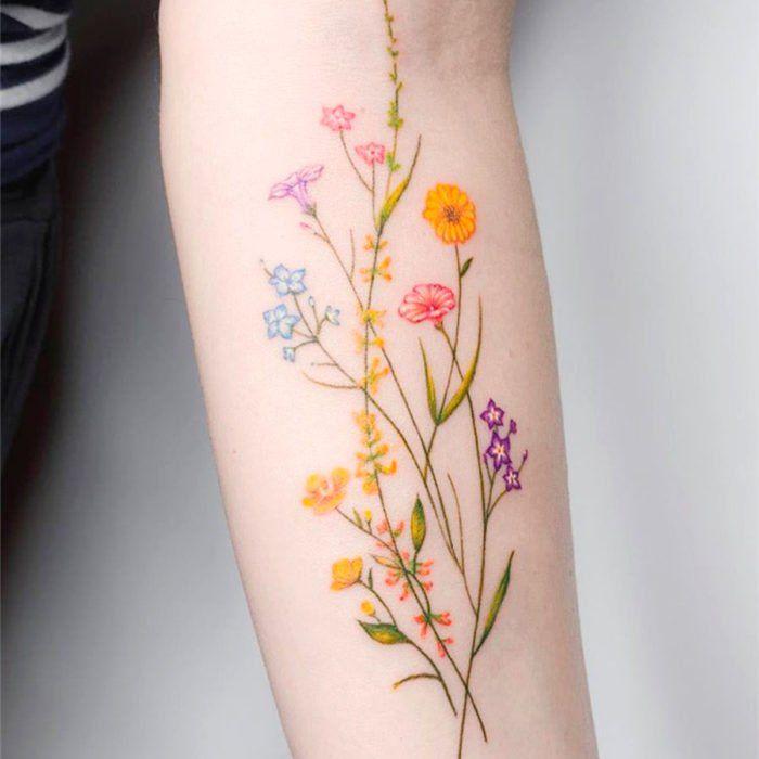 Tatuaje de flores en el que se ve el crecimiento de diferentes tipos de plantas sobre el antebrazo