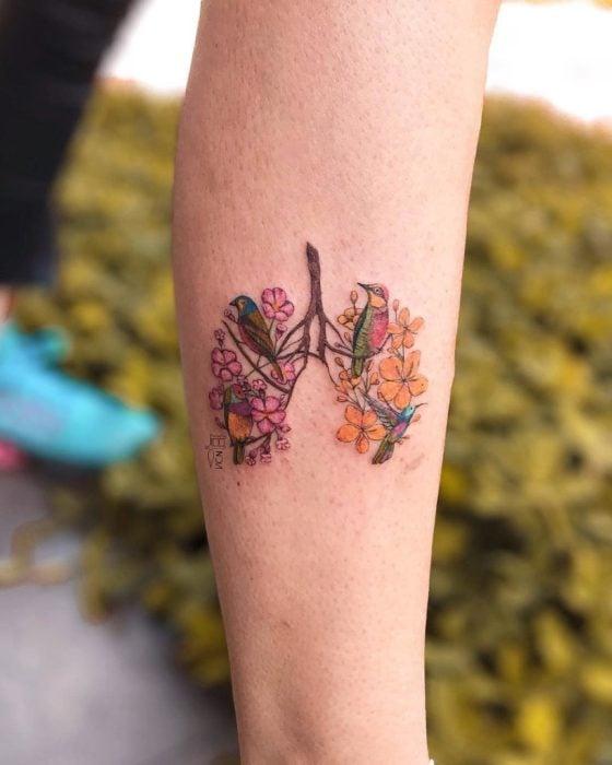 Tatuaje de flores en el antebrazo donde es la silueta de unos pulmones que llevan dibujados varias plantas