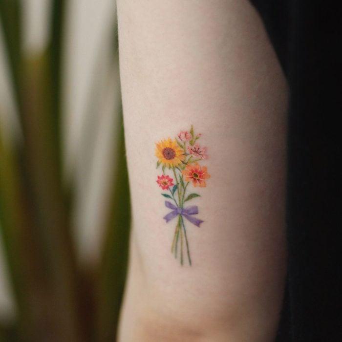Tatuaje de flores en el brazo, es un ramo de flores atado con un listón morado