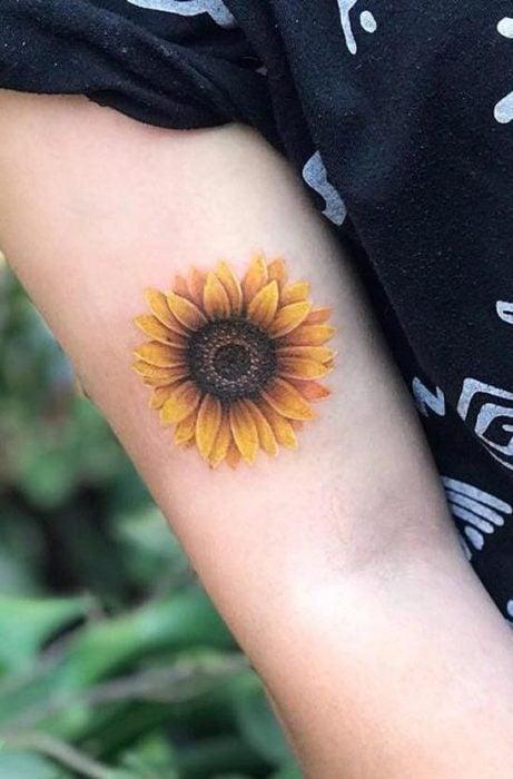 Tatuaje de flores en el brazo de un girasol gigante