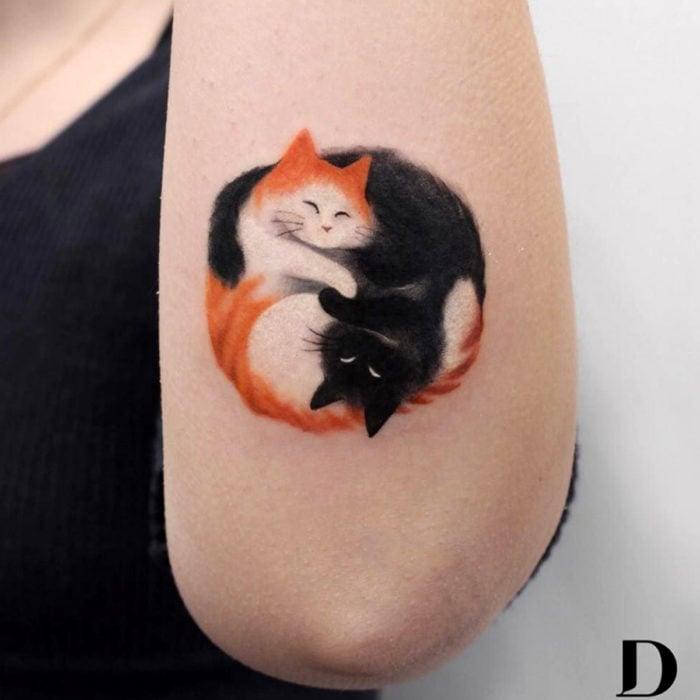 Tatuajes de gatos; tatuaje en el brazo de felinos abrazados, anaranjado y negro