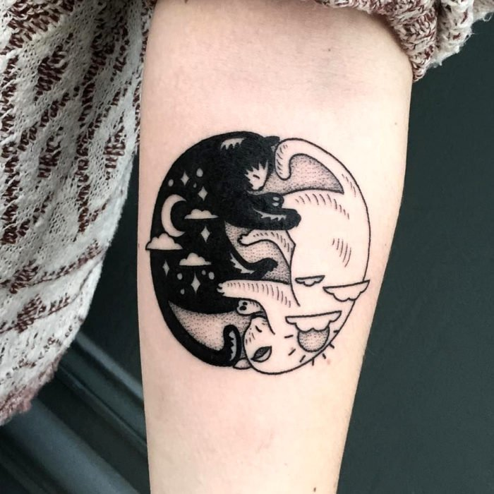 Cat tattoos; Arm tattoo of black and white felines sleeping like yin and yang