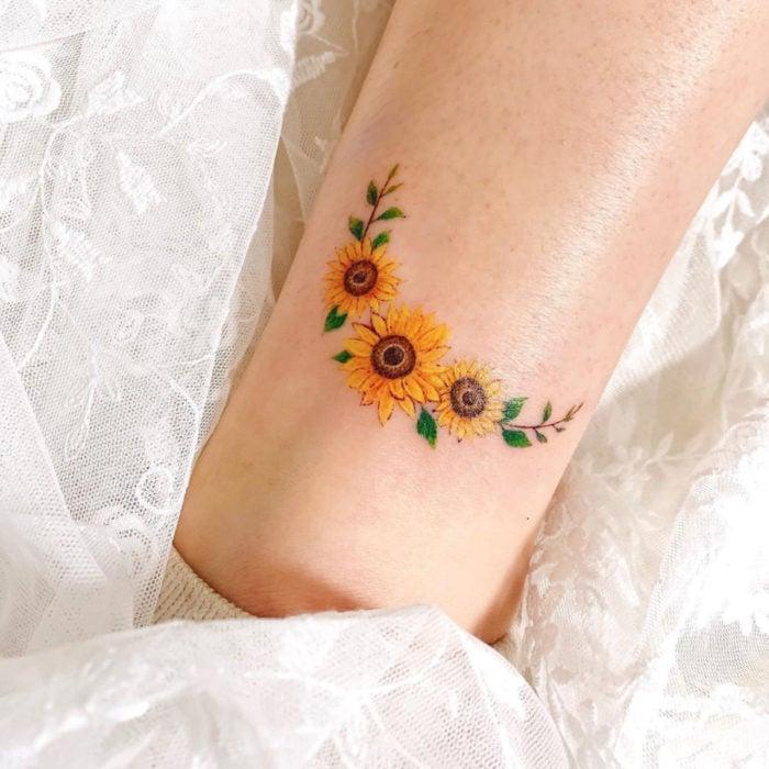 Tatuaje de corona de girasoles pequeños en el brazo
