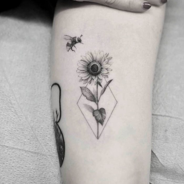 Sunflowers tattoo with bee on the arm in black and white