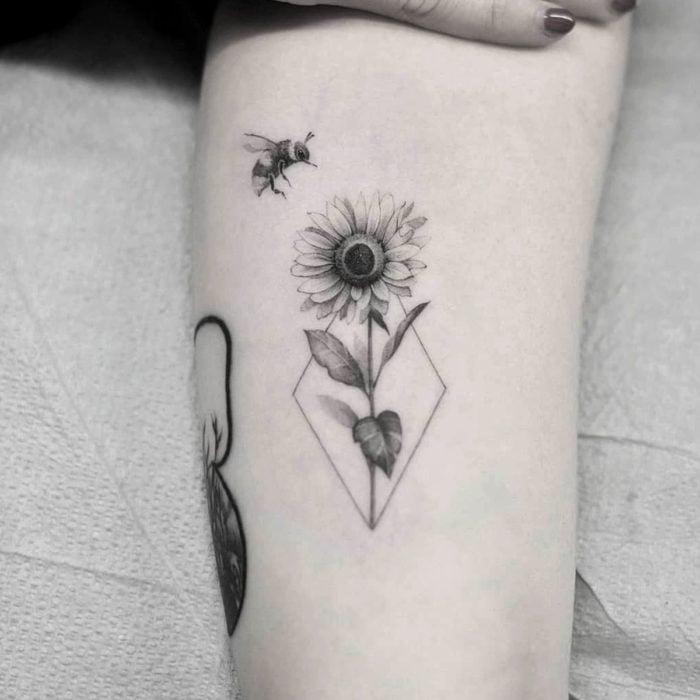 Tatuaje de girasoles con abeja en el brazo en blanco y negro