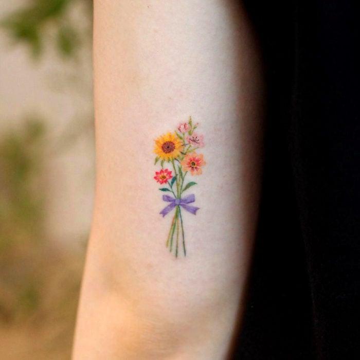 Tatuaje de girasoles miniatura en colores pastel en el brazo