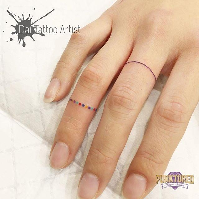 Chica con una línea y puntos tatuados como anillos en sus dedos