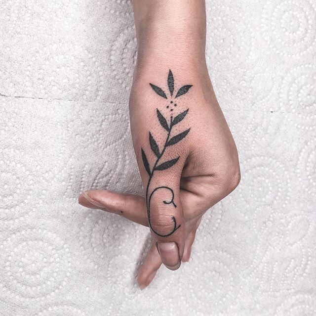 Girl with a tattoo of some leaves on her thumb