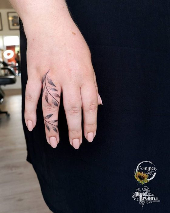 Girl with a hello tattoo that goes from the tip of her middle finger to her wrist