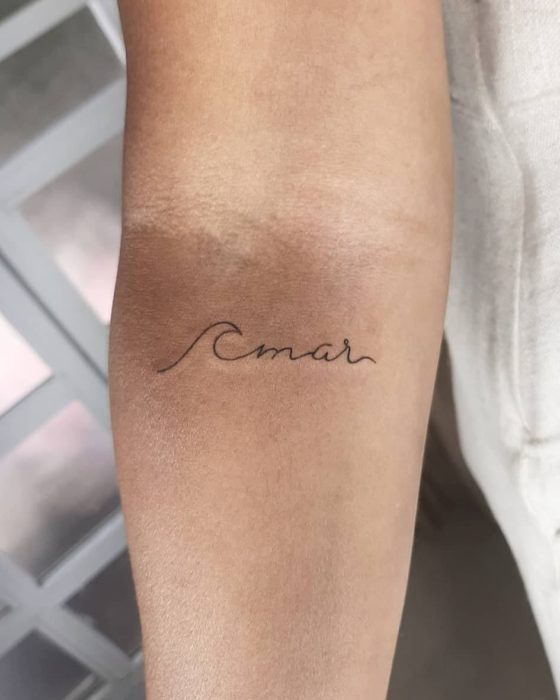 Minimalist tattoo of the word sea next to a wave