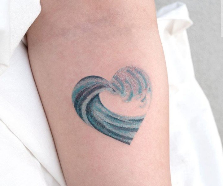 Heart-shaped tattoo with those of the sea inside in blue tone